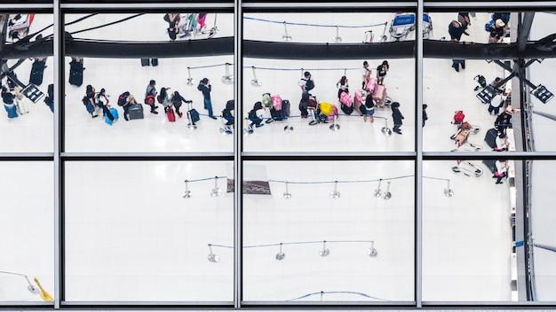 Отражение стекла вид сверху людей в соответствии с багажом и портфель, чтобы путешествовать