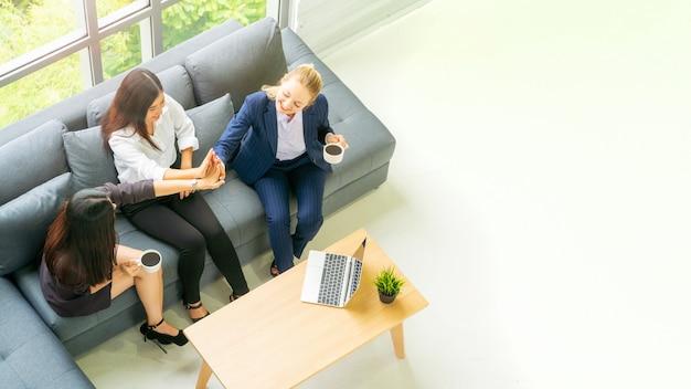 С высоты птичьего полета бизнес-леди говорить и сидеть на сером скамейке диван с черным кофе пить.