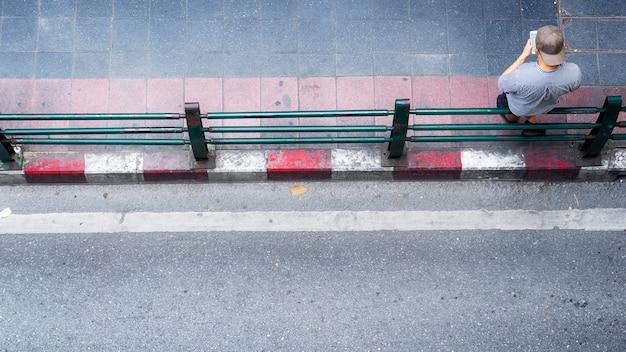 男の平面図は携帯電話を使用し、屋外の歩行者通りに立っています。