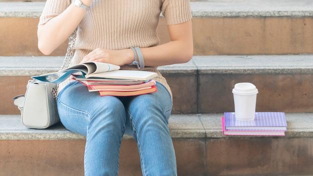 教育本とコーヒーカップを持つ学生十代の少女は、階段の歩行者の上に座る。