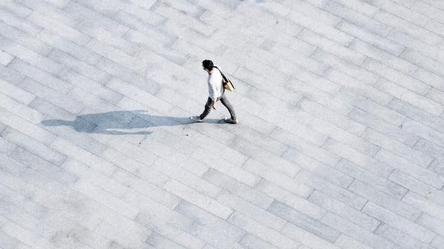 社交的な家族や友人の人々は、オープンスペースの風景の中で歩行者を越えて歩きます。