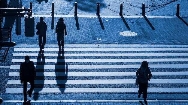 シルエットの人が横断歩道を歩く