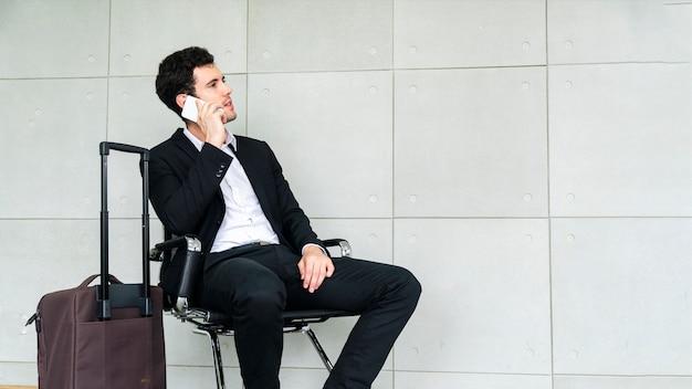 ビジネスの男性はスーツケースと出張旅行を待っているとスマートフォンを呼び出す椅子に座っています。