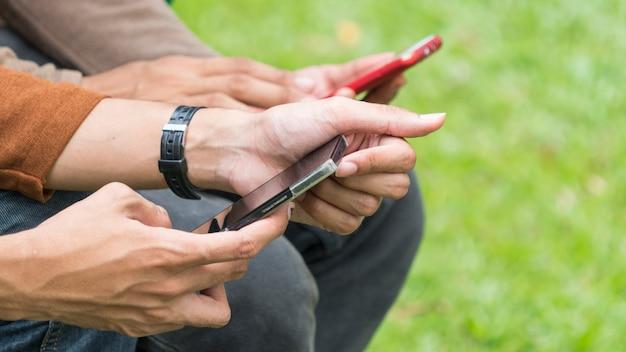Группа в составе смартфоны с руками людей, устройством технологии фокуса и концепцией наркомании мобильного устройства.