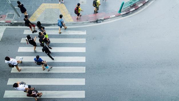 人々の群衆は、トップビュー、鳥瞰図から、街の通りで横断歩道を歩きます。