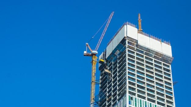 タワー建築の上部に広告のための空白の白い看板と青い空を背景クレーンとビル建設現場。