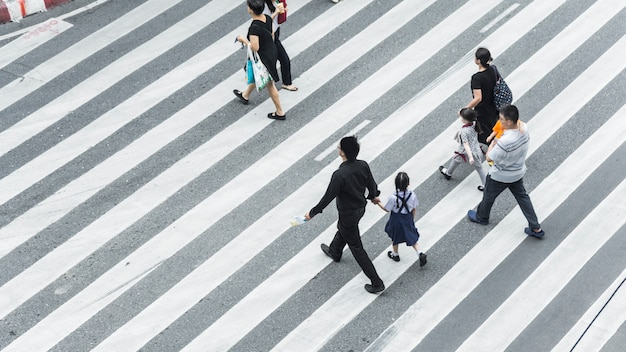 人々の群衆と子供連れの家族のグループが街の通りで横断歩道を歩く