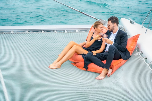 素敵なドレスとスイートの豪華でリラックスしたカップルの旅行者は、ビーンバッグの上に座り、クルーズヨットの一部でワインを飲みます。