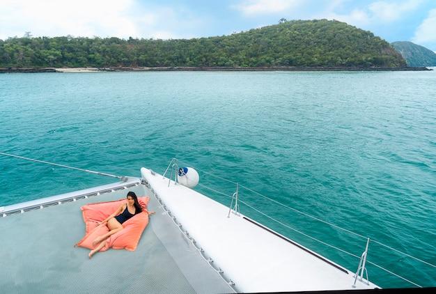 Девушка портрета сексуальная азиатская в славном черном бикини кладет ослаблять на сумке фасоли в части круизной яхты.