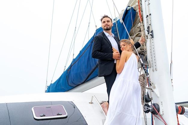 素敵なドレスとスイートの豪華でリラックスしたカップルの旅行者がクルーズヨットの一部に立つ