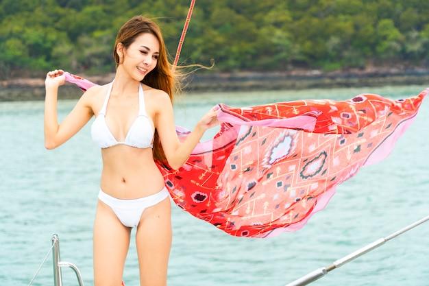 ボートヨットの上に赤い浮遊布立っているを保持している女性