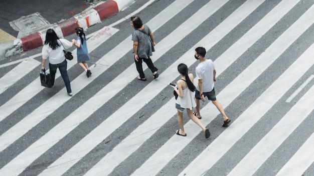人の群衆と子供連れの家族のグループが街の通りで横断歩道を歩きます。
