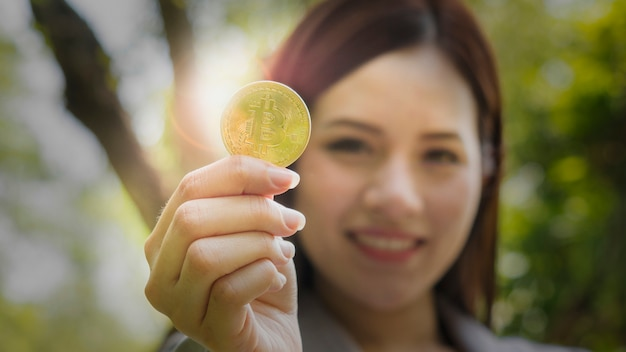 デジタル通貨を表示するカジュアルな実業家の手にビットコイン。