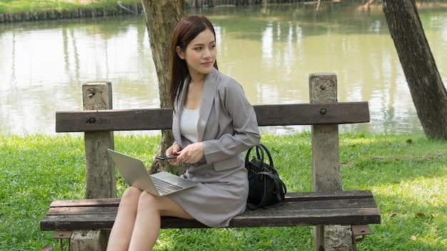 ビジネスの女性はコンピューターを使用し、庭の公園で考えます。