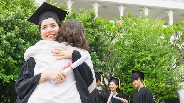 卒業式のガウンと帽子を持つ女子学生は、お祝い式で親を抱擁します。