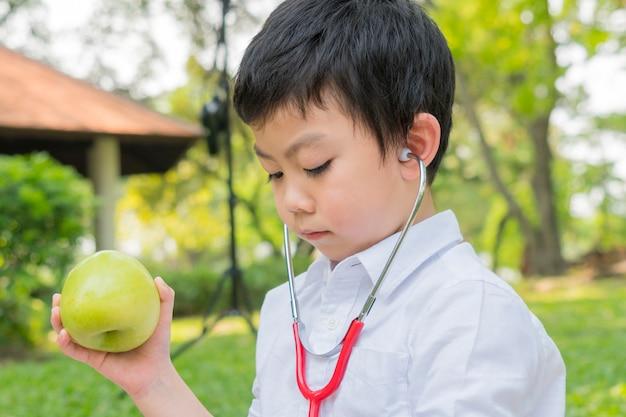 Мальчик использует стетоскопы и играет с фруктами зеленого яблока
