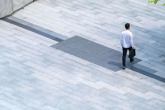上部の空中写真は、屋外の歩行者用コンクリート地面で歩行者を横切って歩きます。