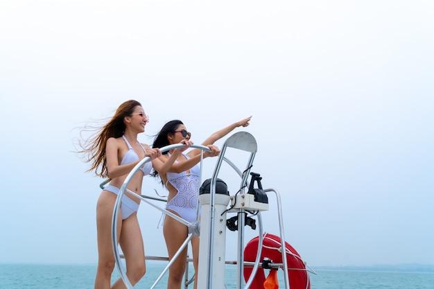 ビキニセクシーな女の子スタンドと海と空の背景を持つボートヨットのドライバー手ステアリングホイールとダンス
