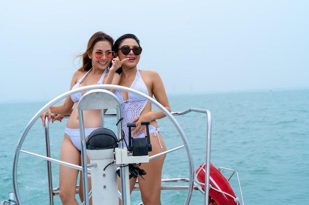 Бикини сексуальная девушка стоит и танцует с водителем рулевого колеса на лодке яхты на фоне моря и неба