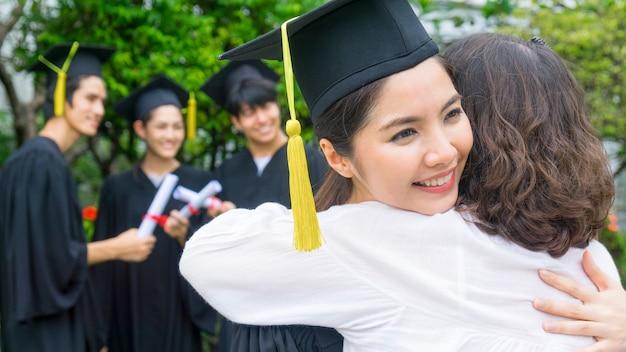 Девочка-студентка с выпускным платьем и шляпой обнимает родителя на церемонии поздравления.