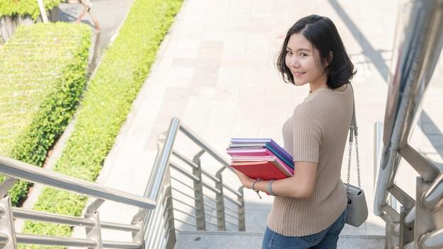教育本と学生ファッションの十代の少女