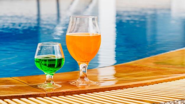 スイミングプールでの夏の飲み物のカラフルなカクテル