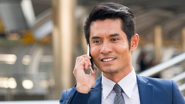 Портрет красивого делового человека, одетого строго в костюмы, используют смартфон.