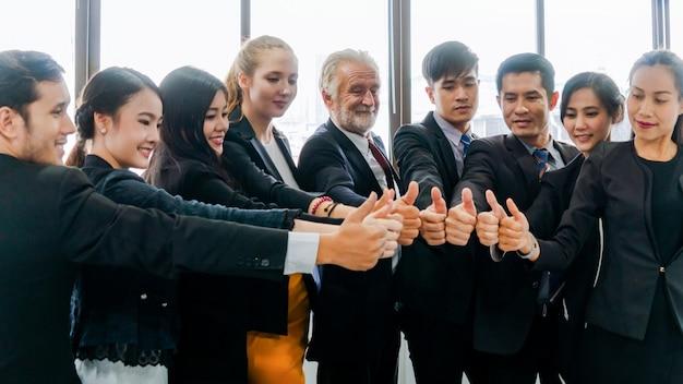 ビジネスチームワークは、合意と屋内オフィスでの成功のために一緒に親指を立てます。チームの仕事のビジネスコンセプト。