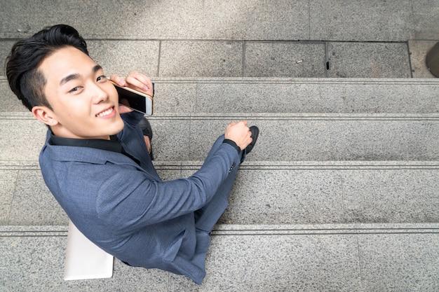 ビジネスの男性の平面図は、スマートフォンの手を使用して、階段の歩行者に座っています。