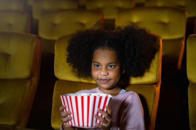 アフリカの女の子は映画館の座席で映画を観たり観たりしています。顔は幸せで楽しいです。
