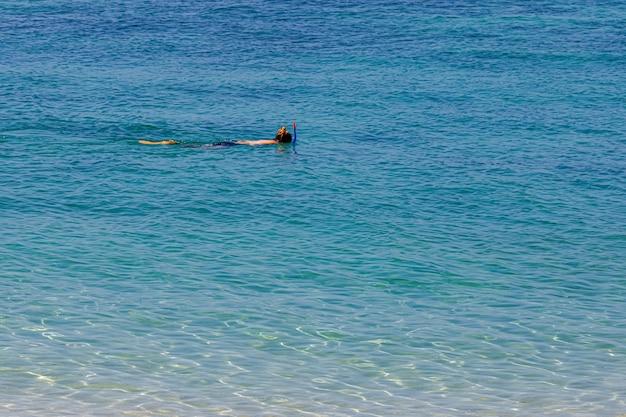 Одна женщина занимается подводным плаванием для мелких коралловых рифов