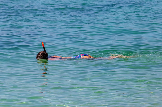 一人の女性が浅いサンゴ礁でシュノーケリングをしています