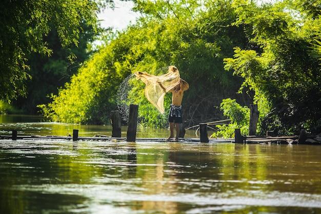 Азиатские рыбаки на деревянных мостах рыболовных сетей утром.
