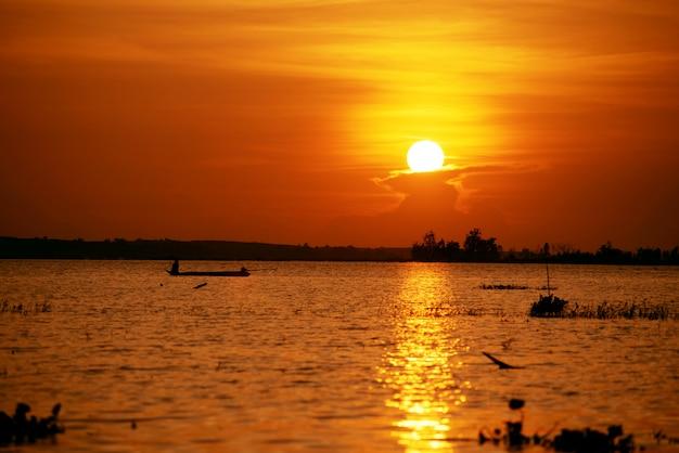 アジアの漁師はタイの沼でボートに乗って釣りで魚を捕まえます。