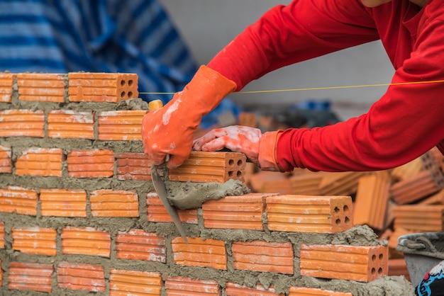 Рабочий-строитель кладя кирпичи и строя стену в промышленное место.