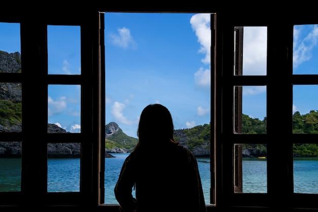 海の景色を望む窓から見ている女性のシルエット。