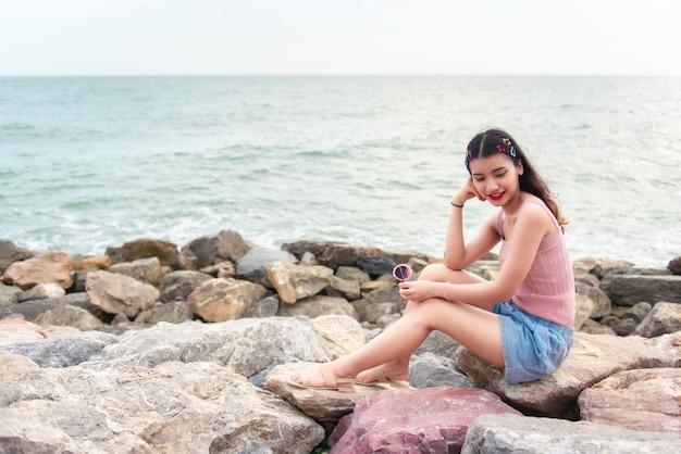 海のほとりの岩の上に座っているセクシーな女の子。