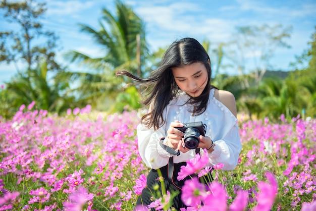 カメラでコスモスの花畑で楽しんでいる女性写真家の写真。