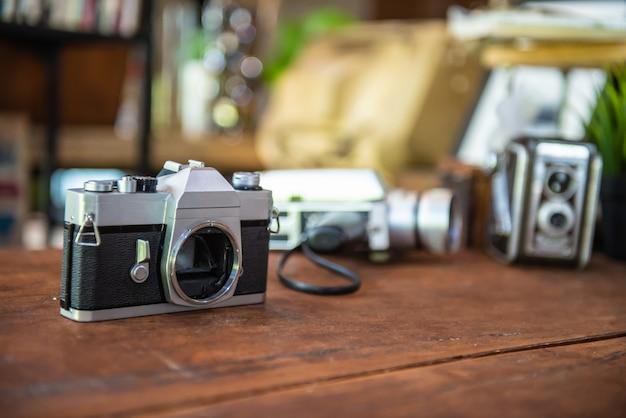 コーヒーショップで木製のテーブルの上の古いカメラ。休日のコーヒーショップで人々の生活。