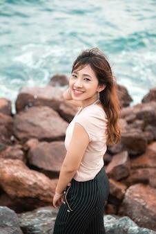 海の海岸の岩の上に座っているセクシーな女の子。海の海岸の大きな岩の上に座っています。
