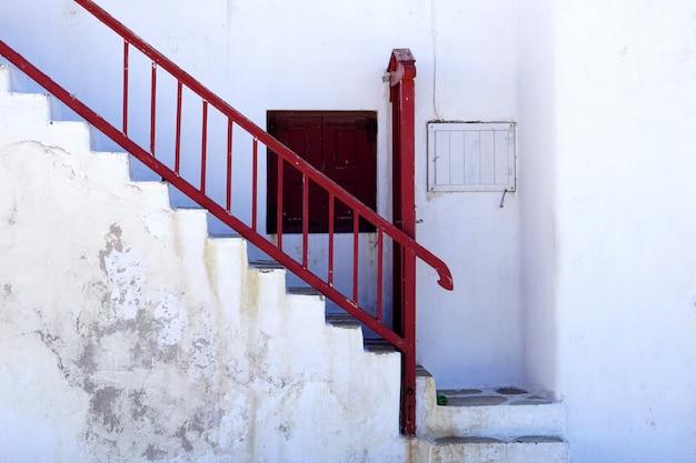 古い剥離白塗りの家とギリシャの赤い梯子