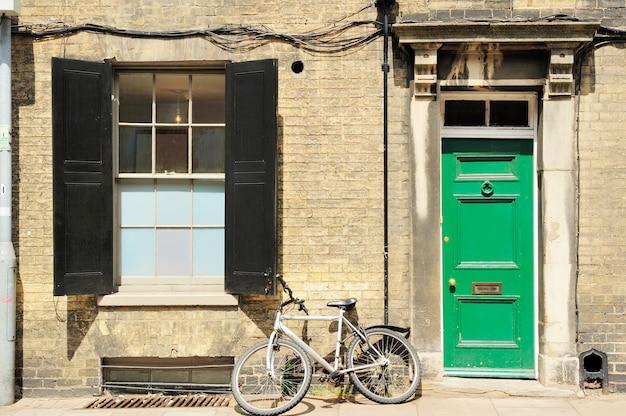 イギリスのカラフルなドアが付いている家によって傾いている古い古典的な自転車
