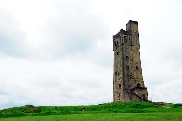 Башня виктории, замковая гора в облачном небе в англии хаддерсфилд
