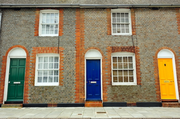 イギリスのカラフルなドアと古い古典的なレンガの壁