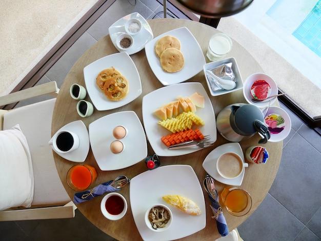 朝の丸い木製のテーブルでの朝食のセット