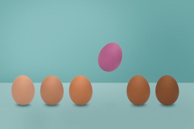 青い背景にピンクの卵と卵の色合いの色を飛んでいます。最小限のイースターの考え。
