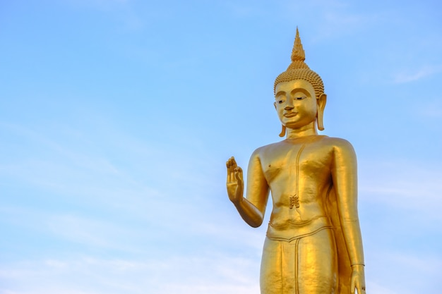 Золотой будда на фоне голубого неба с копией пространства