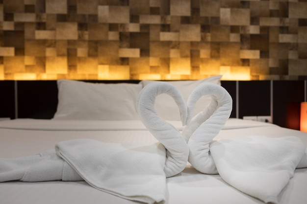 Крупный план сложенных лебедей, птица из свежих белых банных полотенец на простыне в отеле