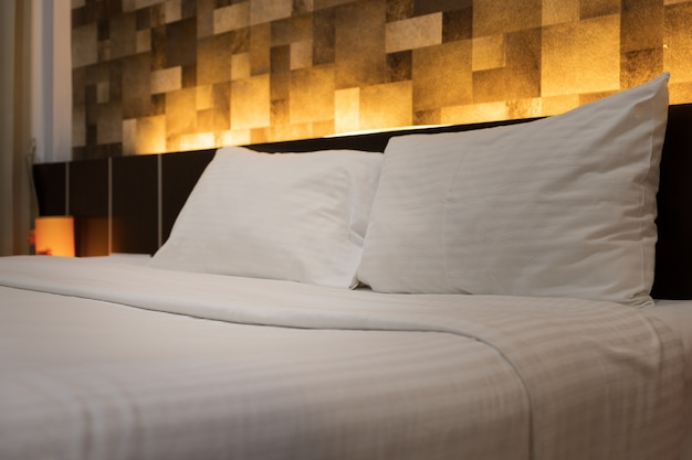 ホテルのルームサービスの手はホテルのベッドの上に白い枕を設定します