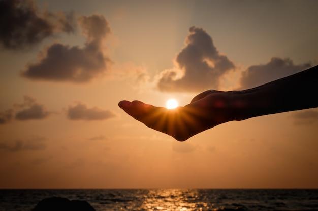 Силуэт руки ловить падающее солнце.